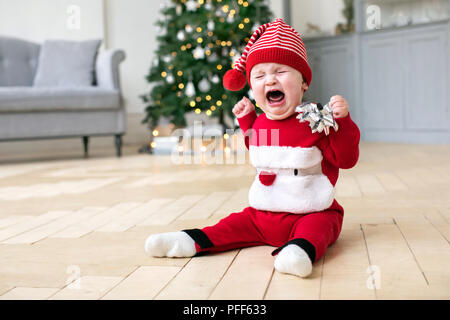 Baby in Cristmas costume crying on floor - Stock Photo