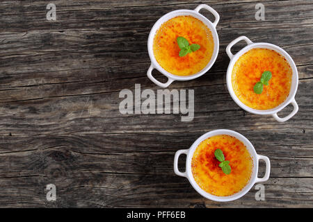 Creme brulee - french dessert of custard topped with caramelized sugar and decorated with mint leaves in white ceramic souffle dishes on old rustic ta - Stock Photo