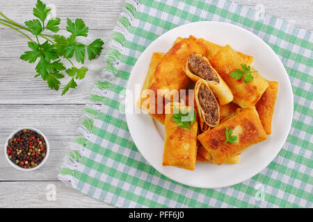 fried in olive oil delicious Crispy and hot Crepes filled with minced Meat and liver on white plate on old wooden table with mix of pepper corn and pa - Stock Photo