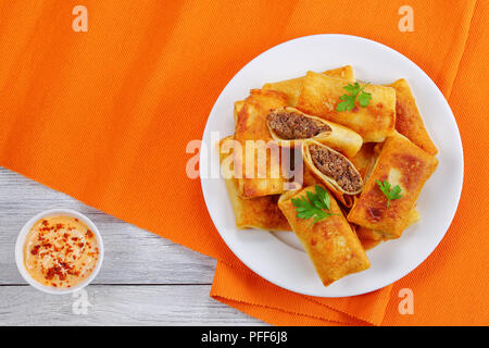 fried in olive oil delicious Crispy and hot Crepes filled with minced liver and rolled up on white plate on old wooden table with paprika mayonnaise s - Stock Photo