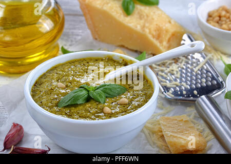 close-up of  homemade sauce pesto in bowl with ceramic spoon and ingredients - fresh basil leaves, cheese, pine nuts, olive oil, garlic on wooden tabl - Stock Photo