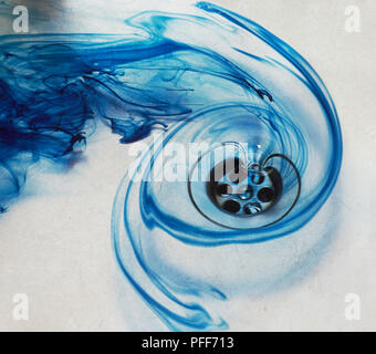 A blue swirl of water spinning down a drain - Stock Photo