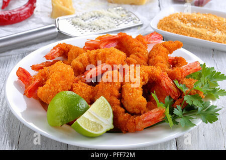 light and crispy crunchy parmesan bread crumbs coating Fried Shrimps on white plate on wooden table with bread crumbs, parmesan cheese, grater garlic  - Stock Photo