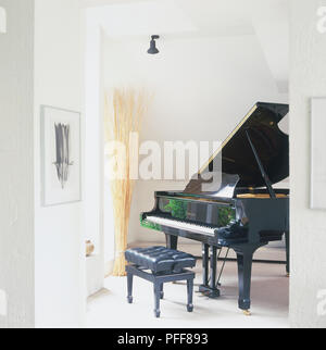 Grand piano with padded stool in corner of attic room. - Stock Photo