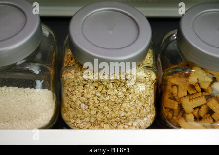 Various raw cereals, grains, beans and pasta for healthy cooking in glass jars on kitchen shelf, white background. Clean eating, vegetarian, vegan, ba - Stock Photo