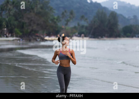 Young slim woman running barefoot on the ocean beach at sunset - Stock Photo