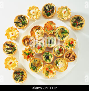 Various small quiches on a platter and in a semi-circle around it, view from above. - Stock Photo