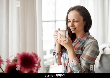 Happy girl with a mug of fragrant coffee in hands. Good breakfast at home in the living room by the window. Free space for text. - Stock Photo