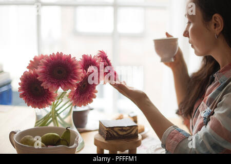 Woman with a mug of coffee, a good morning at home. Breakfast and fragrant coffee. The interior is cozy and the flowers. Free space for text. - Stock Photo