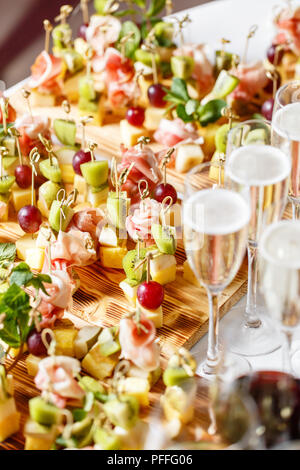 solemn happy new year banquet. Lot of glasses champagne or wine on the table in restaurant. buffet table with lots of delicious snacks. canapes, bruschetta, and little desserts on wooden plate board - Stock Photo