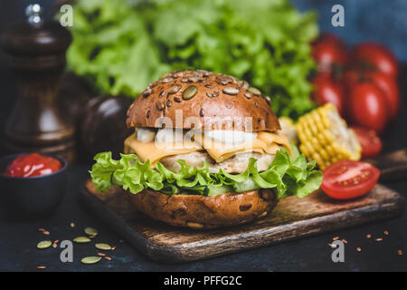 Tasty Chicken Burger On Wooden Serving Board. Cheeseburger With Cheese, White Sauce, Lettuce, Tomatoes. Closeup view, Selective focus - Stock Photo