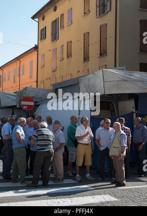 Old men gathering by busy street for a chat on market day in the small city of Castel San Pietro Terme, Metropolitan City of Bologna, Italy, Europe. - Stock Photo