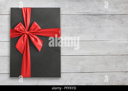 Gray gift box with red ribbon on white wood view from above, space for text - Stock Photo