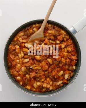 Baked beans, sliced sausage, onions and bacon in frying pan with wooden spoon - Stock Photo
