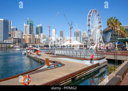 Ferris wheel in Darling harbour and Sydney city centre skyline,New South Wales,Australia - Stock Photo
