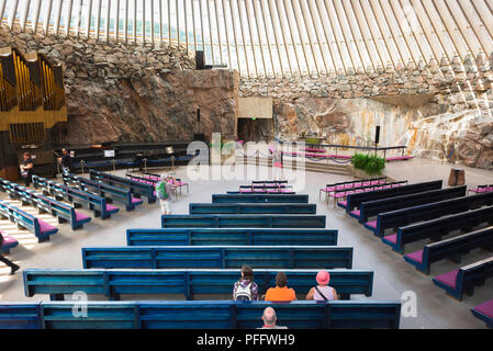 Temppeliaukio Church, view inside the Temppeliaukion Kirkko or 'Rock Church' in central Helsinki showing tourists seated in its blue pews, Finland. - Stock Photo