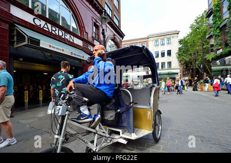 Rickshaw driver on his mobile phone by Covent Garden underground station, London, England, UK. - Stock Photo