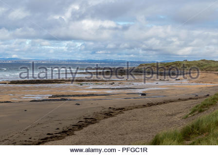 A deserted Fanore beach Co. Clare, Republic of Ireland with wind turbines on the far side of the estuary. - Stock Photo