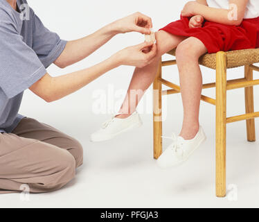 Adult sticking a plaster on girl's knee, close up. - Stock Photo
