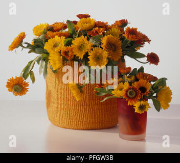 Orange and yellow marigolds in large basket and small glass vase - Stock Photo