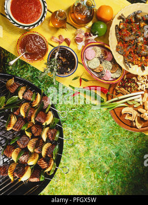 Kebabs on barbecue, table laid with selection of sauces, cheeses, vegetables and fish, view from above. - Stock Photo