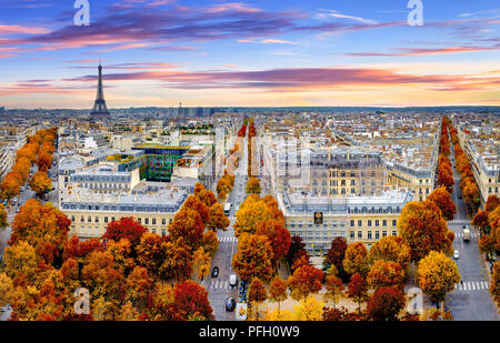 Aerial view of Paris in late autumn at sunset.Red and orange colored street trees. Eiffel Tower in the background. Paris, France - Stock Photo