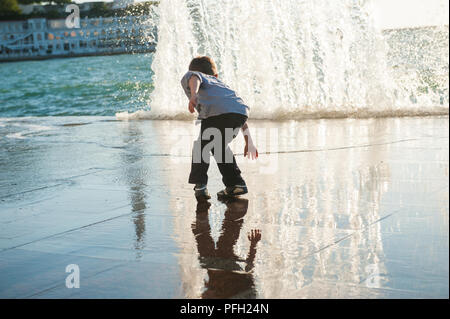 funny small kid escaping from huge wave in city port during autumn storm - Stock Photo