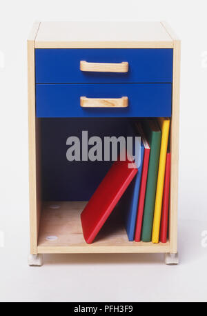Small wooden cabinet with two blue drawers and colourful books stacked on the bottom shelf, front view - Stock Photo