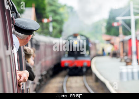 Rear view of ticket inspector (taken whilst on board) leaning out of vintage carriage as train approaches station. Second steam engine is  approaching. - Stock Photo