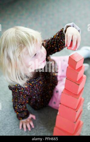 Girl stacking red wooden blocks in size order - Stock Photo
