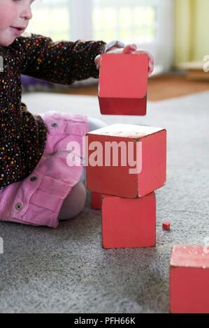 Girl stacking red wooden blocks, sitting on carpet, close-up - Stock Photo