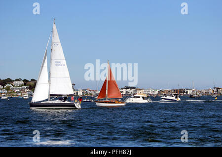 Sandbanks, Dorset, England - June 02 2018: Two sailing boats, and two motor boats, sailing through Poole Harbour in line, on a clear sunny summer day, - Stock Photo