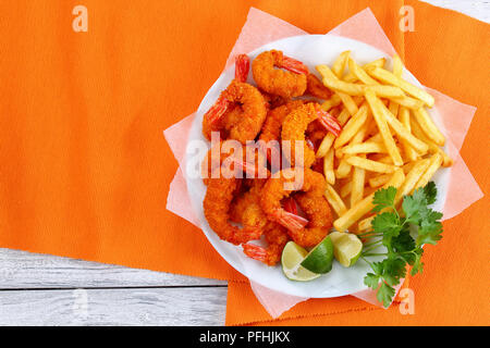 delicious light and crispy crunchy parmesan breaded Fried Shrimps with lime wedges, french fries and parsley on white plate on wooden table, street fo - Stock Photo
