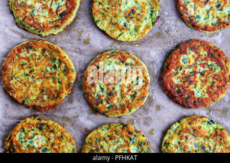 delicious baked in oven delicious zucchini fritters on baking paper, healthy and easy vegetarian recipe, view from above - Stock Photo