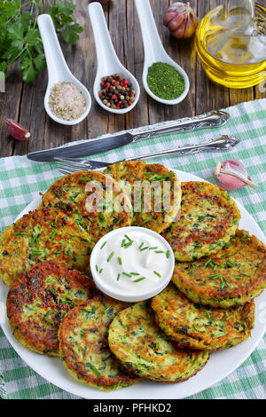 crispy zucchini fritters sprinkled with finely chopped chives on platter with sour cream, on old dark wooden table with ingredients on background, veg - Stock Photo