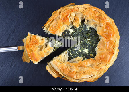delicious golden crust hot greek spinach feta cheese pie or spanakopita cut in slices on black slate tray, classic recipe, view from above - Stock Photo