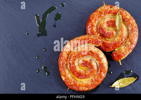 delicious mouth watering german Bratwurst - round fried sausages on wooden skewers on black slate plate with  bay leaves and hot fat drops on backgrou - Stock Photo