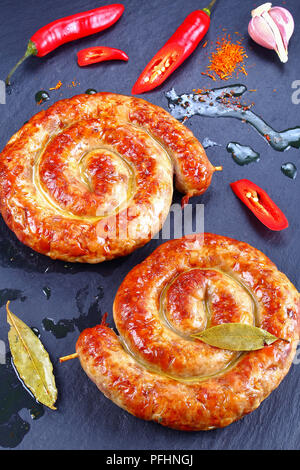 delicious hot bavarian Bratwurst - round fried sausages on wooden skewers on black slate plate with chili peppers and hot fat drops on background, ver - Stock Photo
