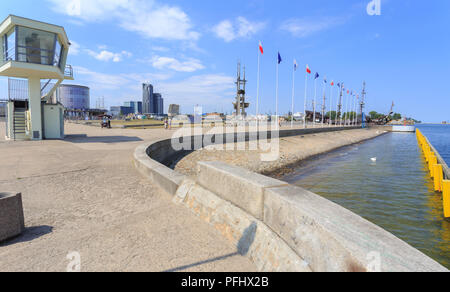 Port of Gdynia - South Pier with the monuments 'Gra Masts' and 'Joseph Conrad'. Skyscraper 'Sea Towers' visible in the distance - Stock Photo
