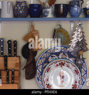 Assorted decorated ceramic mugs and plates plates, knife set, graters and wooden serving spoons, front view. - Stock Photo