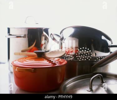 Metal collander, lidded saucepans and pots, wooden spoon, front view. - Stock Photo