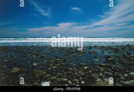 Central America, Costa Rica, Southern Zone, Peninsula de Osa, Parque Nacional Corcovado, Carate, waves crashing over rocks in shallow, translucent waters of shoreline in national park - Stock Photo