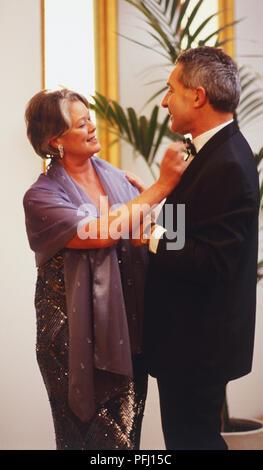 Mature woman adjusting mans bow tie - Stock Photo