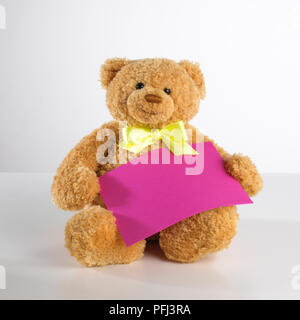 47af4f5c3a3 ... Teddy bear with yellow ribbon tied around neck holding purple envelope