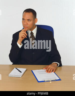 Man in business suit sitting at a desk with his hand on his chin, pen, notepad and clipboard in front of him, front view. - Stock Photo