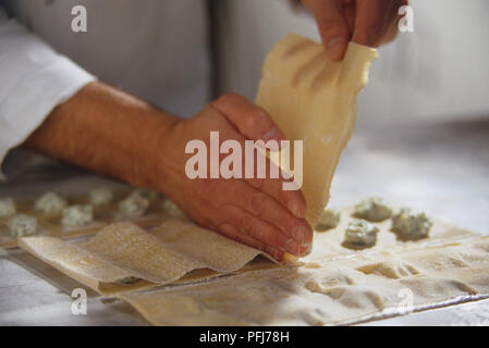 Fresh pasta sheets laid out on kitchen surface, top sheet being pulled over bottom one, covering small round fillings, hand dividing them into sections. - Stock Photo