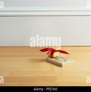Mouse hole in skirting board with decorative rim and cherub, mouse trap with cheese wrapped in a red bow. - Stock Photo