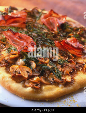 Round pizza with medium-thick, crispy crust, topped richly with sliced mushrooms, ham and rocket, close up, tilted view - Stock Photo