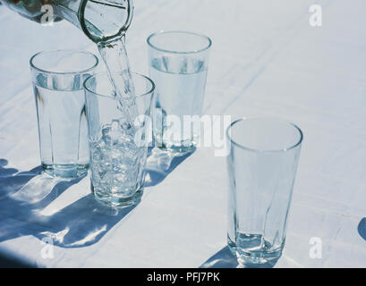 Four tall clear glasses standing on white table cloth, two filled with water, water being poured from glass jug into empty glass - Stock Photo