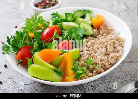 Diet menu. Healthy vegetarian salad of fresh vegetables - tomatoes, cucumber, sweet peppers and porridge on bowl. Vegan food. - Stock Photo